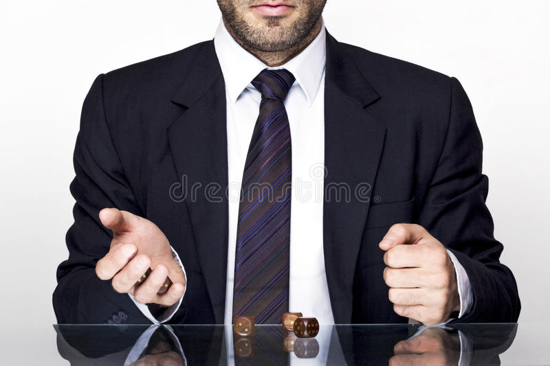 Man gambling. Businessman gambling with wooden dices on a glass table stock photography