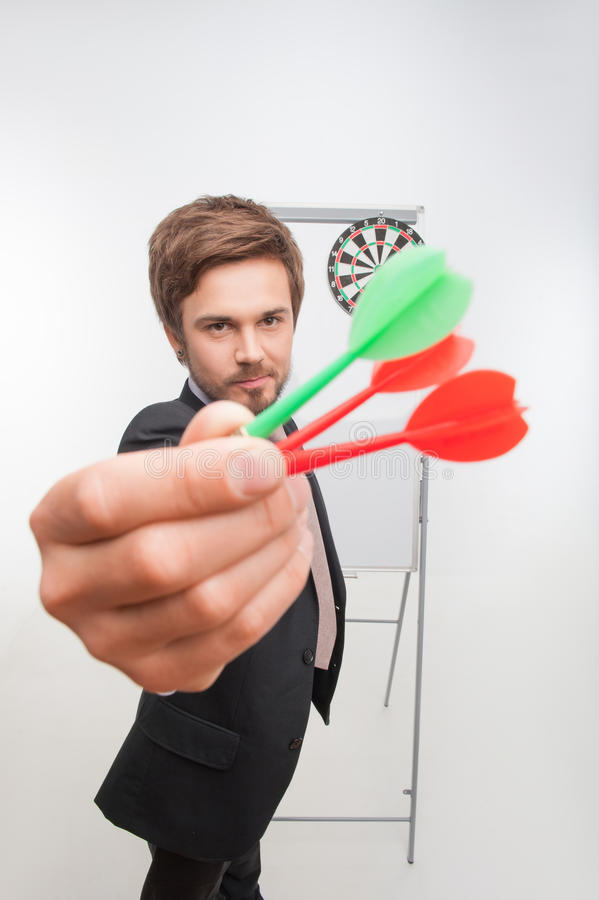 Man and gaming. Half-length portrait of handsome dark-haired man wearing nice costly suit standing near the dartboard and showing us three colorful darts stock photos