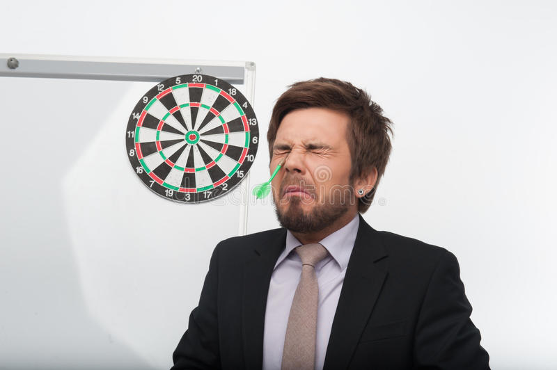 Man and gaming. Poor young man, wearing nice suit standing near the dartboard hitting dart in his eye stock image