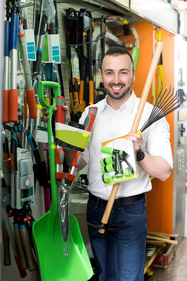 Man with gardening tools in the shop. Smiling man standing next to shop stall with gardening tools in household store stock images
