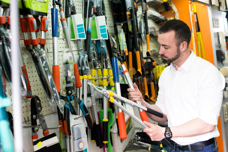 Man with gardening tools in the shop. Young cheerful man standing next to shop stall with gardening tools in household store stock photos