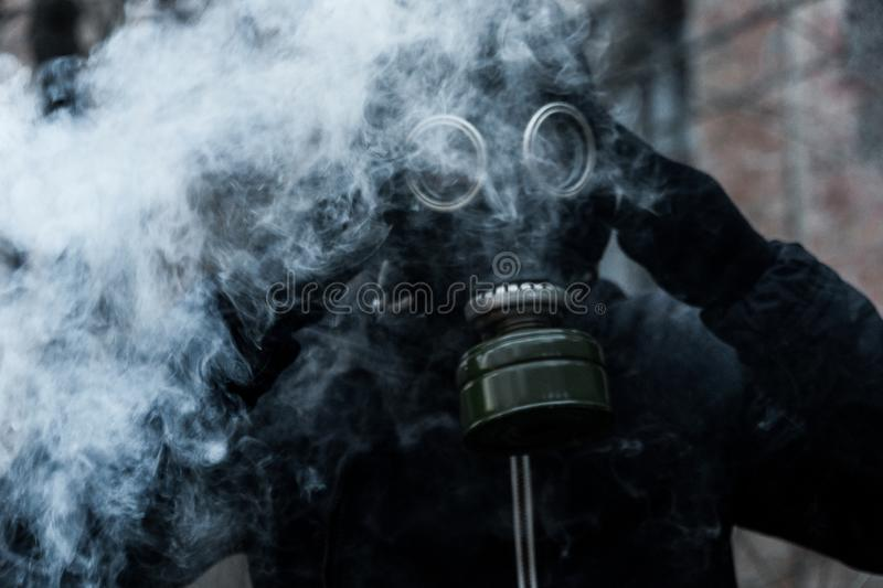 Man in gas mask against disaster background. Pollution concept stock images