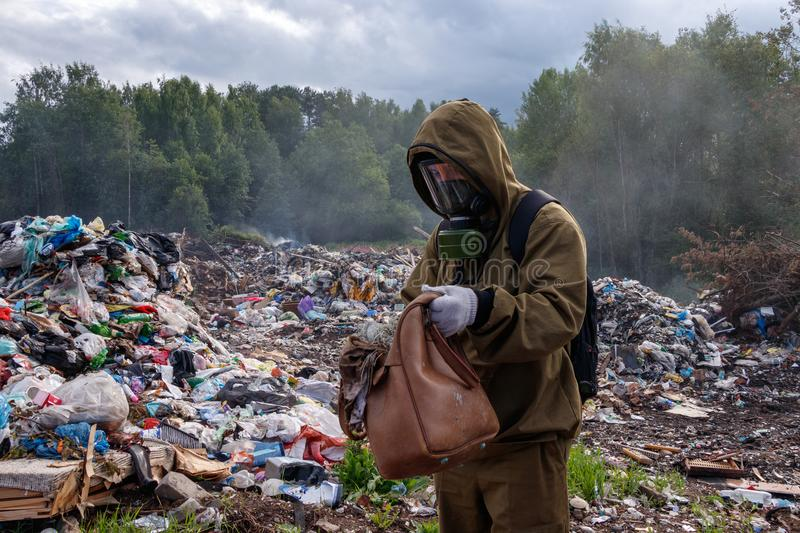 A man in a gas mask examines the contents of the bag. The worker is in the dump. Around burns and smokes plastic garbage.  stock photos