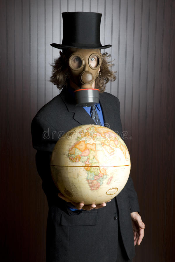 Man with gas mask holding an earth globe stock photos