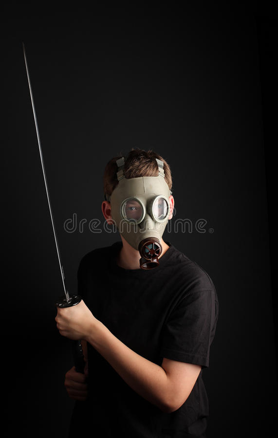 Man with gas mask and katana sword on black background stock photo