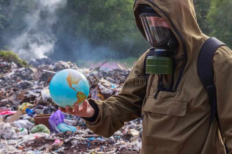 A man in a gas mask looks at when the beautiful planet earth. On the background of burning plastic trash. The concept of environme stock photo
