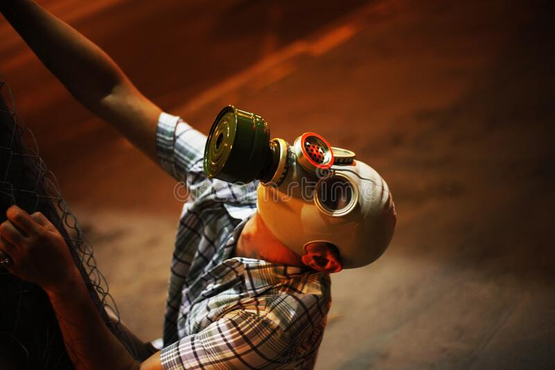 Man in a gas mask on night street.  royalty free stock image