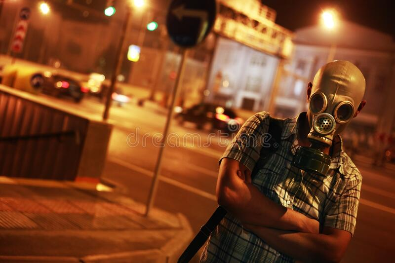 Man in a gas mask on night street.  stock image