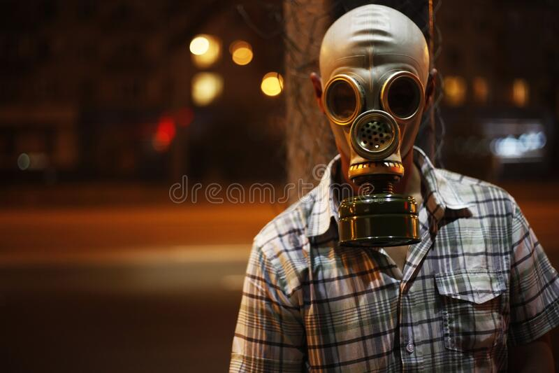 Man in a gas mask on night street.  stock images