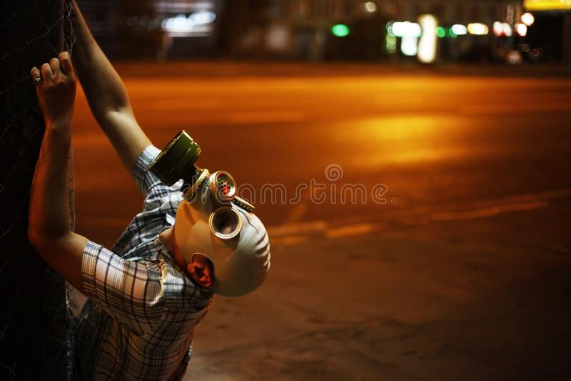 Man in a gas mask on night street.  royalty free stock photo