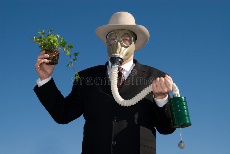 Man with gas mask & plant. Business man wearing a gas mask holding a little plant. It is meant to represent 'Global warming' Blue sky is the background stock photos