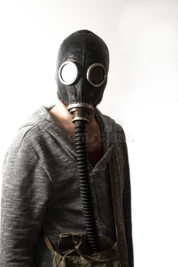 Man Gas Mask. Scary man wearing authentic Russian gas mask with breathing hose royalty free stock image
