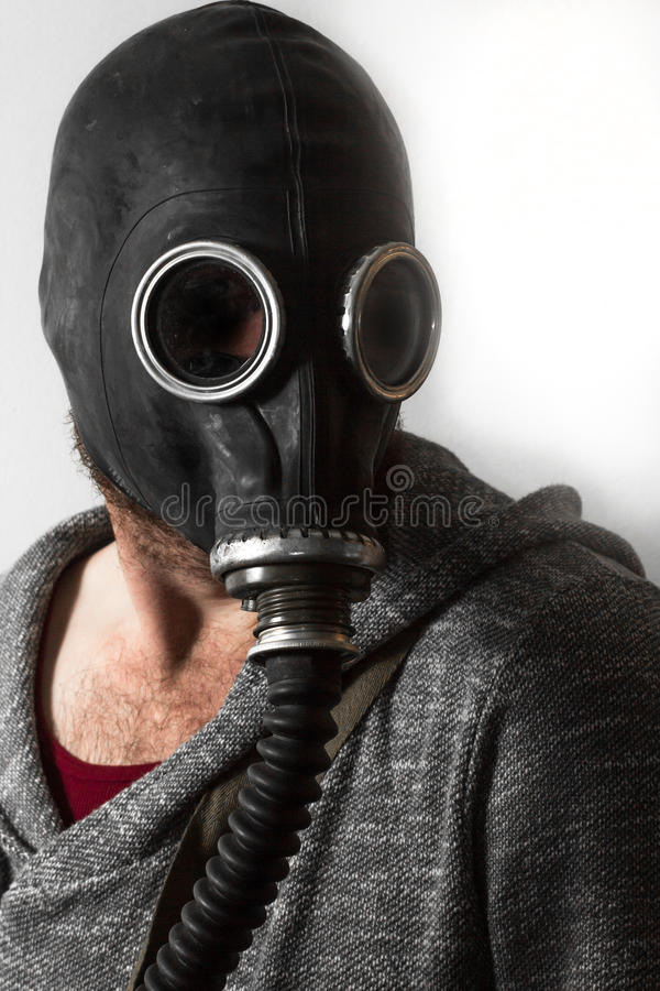 Man Gas Mask. Scary man wearing authentic Russian gas mask with breathing hose royalty free stock photography