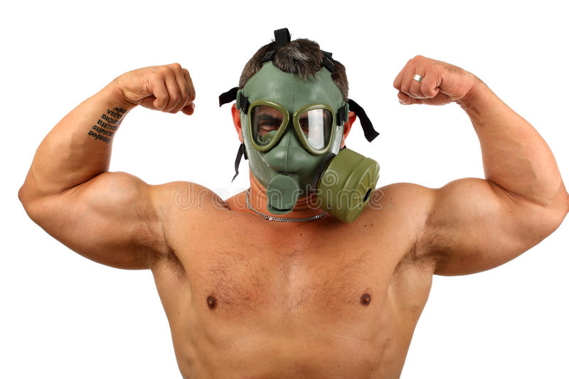 Man in gas mask showing muscles stock image