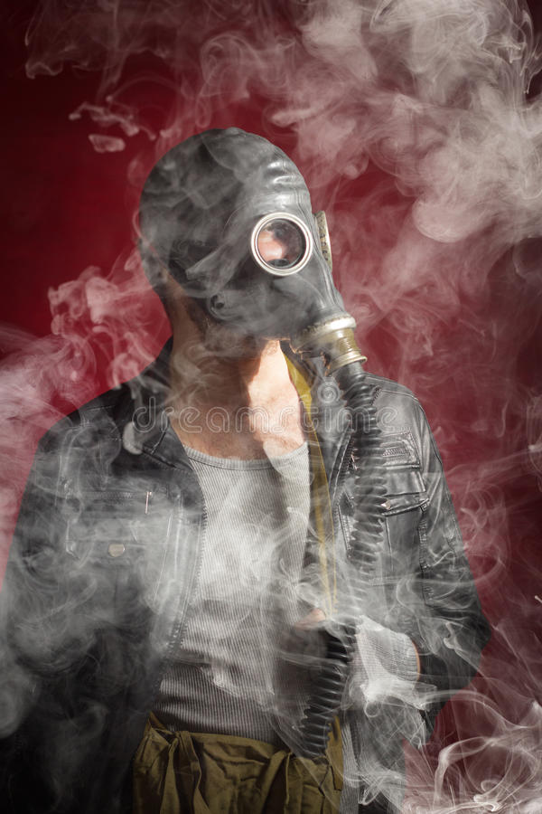 Man Gas Mask Smoke. Scary man wearing authentic Russian gas mask with breathing hose stock photos