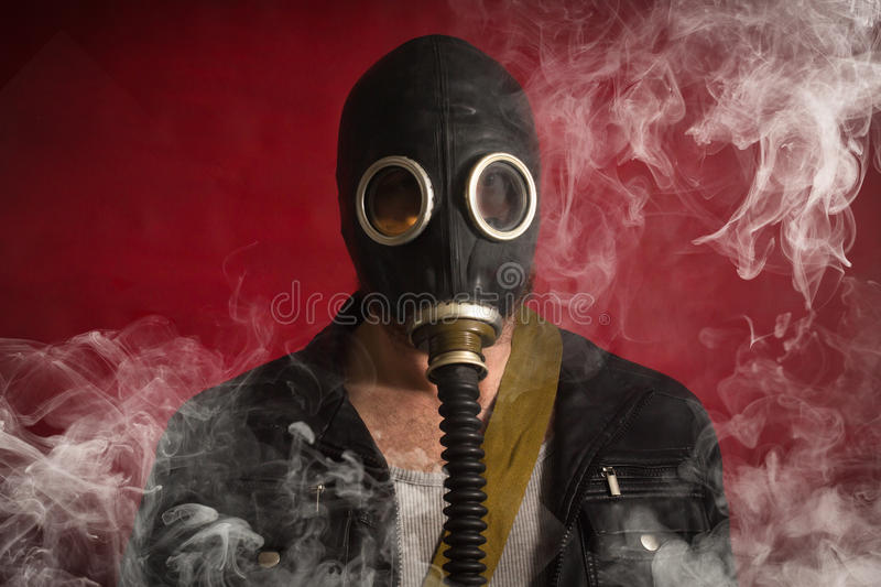 Man Gas Mask Smoke. Scary man wearing authentic Russian gas mask with breathing hose royalty free stock photography