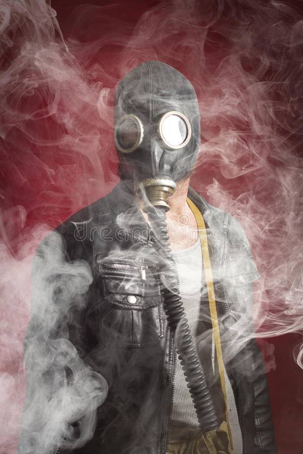 Man Gas Mask Smoke. Scary man wearing authentic Russian gas mask with breathing hose royalty free stock photo