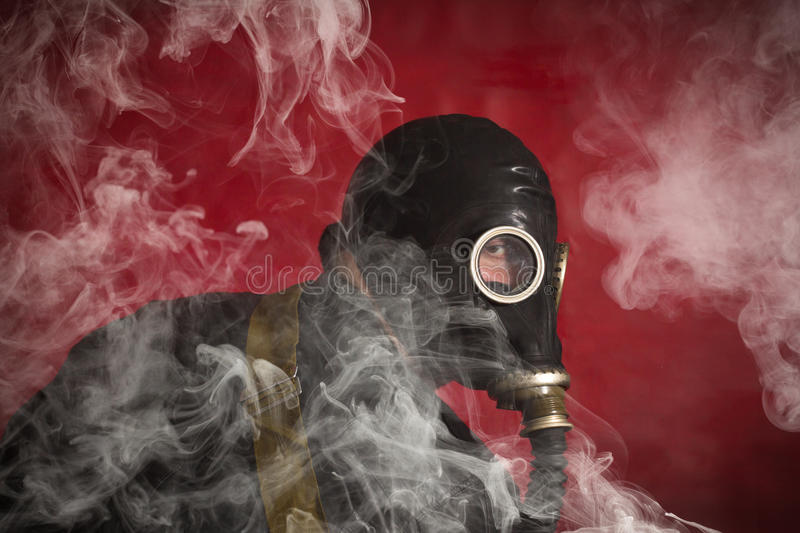 Man Gas Mask Smoke. Scary man wearing authentic Russian gas mask with breathing hose royalty free stock photos