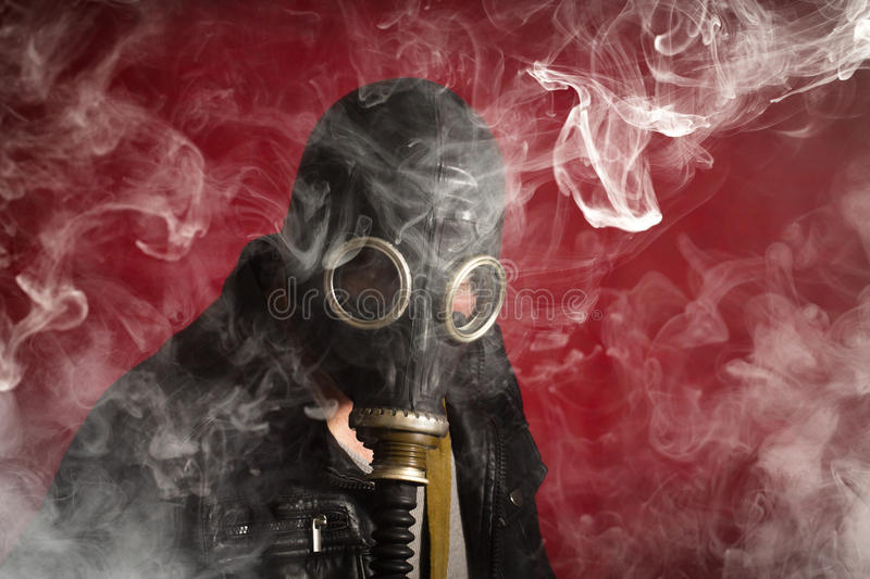 Man Gas Mask Smoke. Scary man wearing authentic Russian gas mask with breathing hose stock image