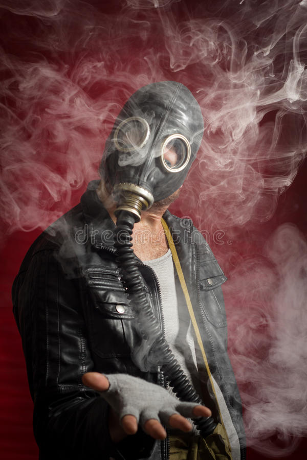 Man Gas Mask Smoke. Scary man wearing authentic Russian gas mask with breathing hose royalty free stock image