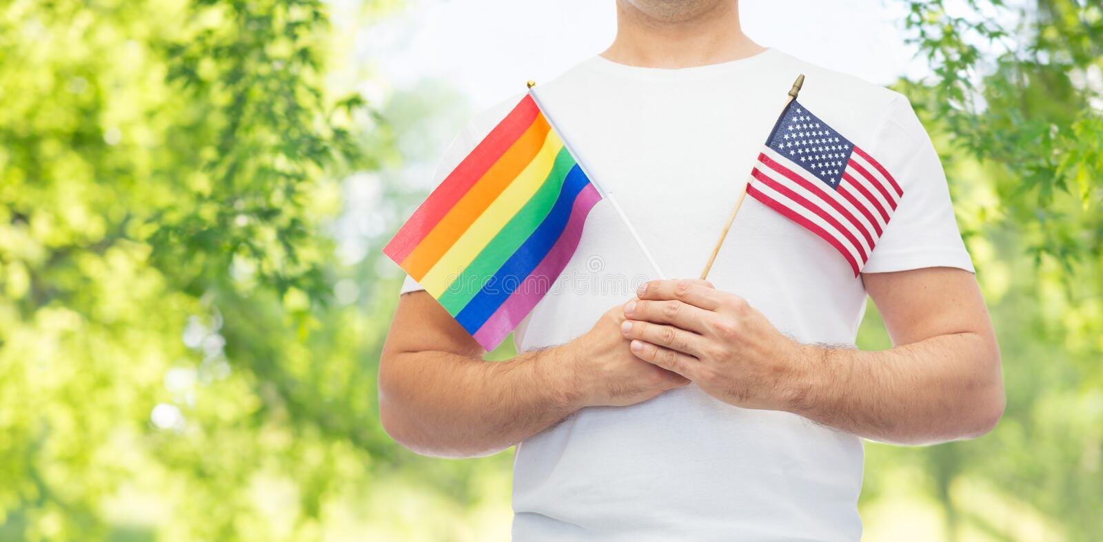 Man with gay pride rainbow flag and wristband stock images