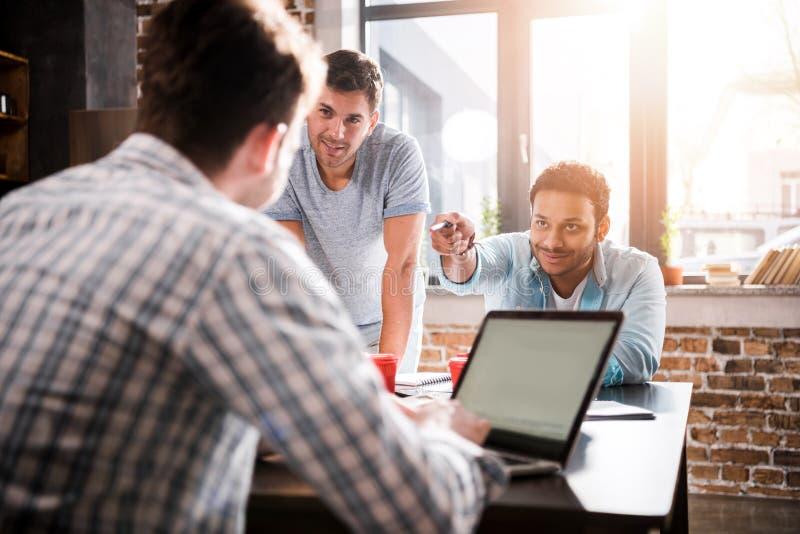 Man genom att använda bärbara datorn medan kollegor som diskuterar projektet, begrepp för små och medelstora företagmöte royaltyfri foto