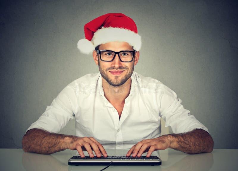 Man genom att använda datoren som shoppar söka efter direktanslutet en julgåva royaltyfri foto