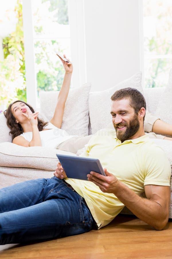 Man genom att använda den digitala minnestavlan medan kvinnan som tar selfie från mobiltelefonen arkivfoton