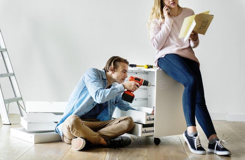 Man genom att använda den elektroniska drillborren för att installera kabinettet och kvinnan som talar på telefonen royaltyfri fotografi