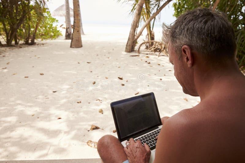 Man genom att använda en bärbar datordator på en strand, över skuldrasikt royaltyfri foto
