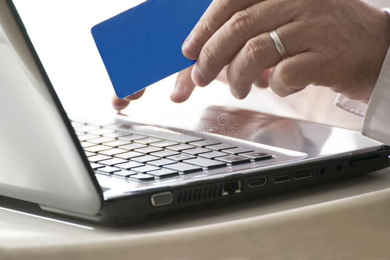 Man genom att använda en online-bankrörelserengöringsduk som rymmer en kreditkort och en bärbar datordator tomt kopieringsutrymme royaltyfri bild