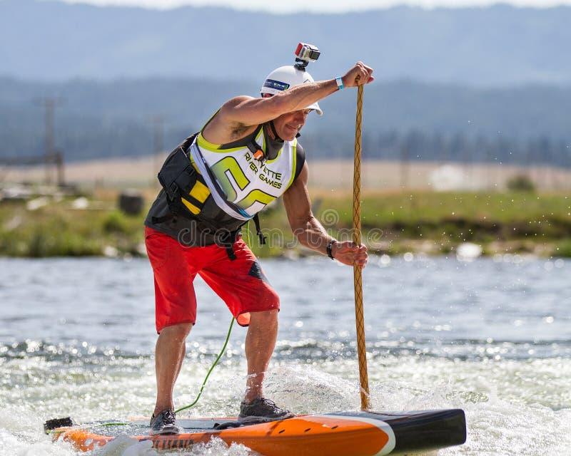 Man genom att använda en paddleboard för att få ner floden arkivfoton
