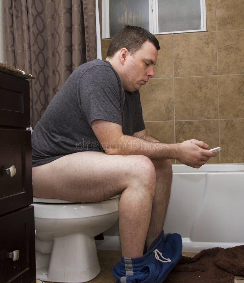 Man genom att använda hans telefon, medan genom att använda badrummet royaltyfri foto