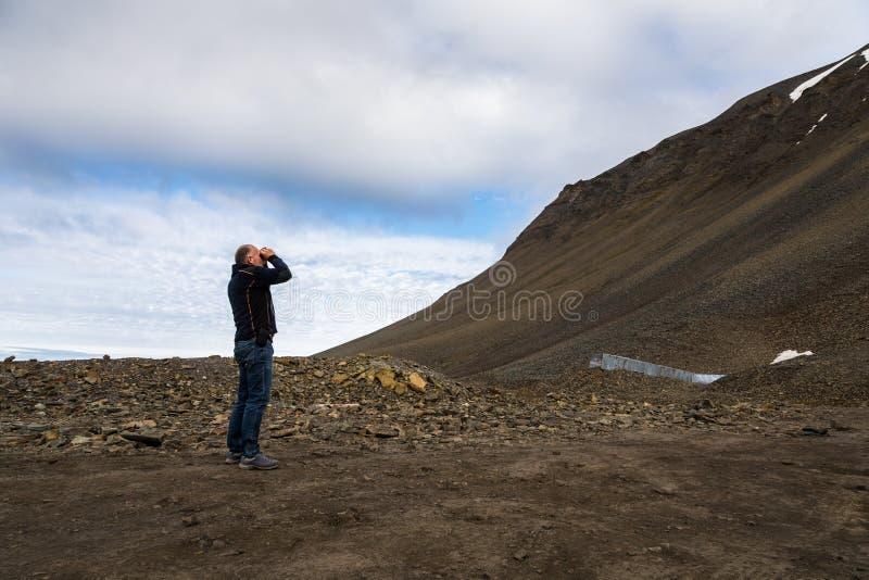 Man genom att använda kikare i bergen på Svalbard fotografering för bildbyråer