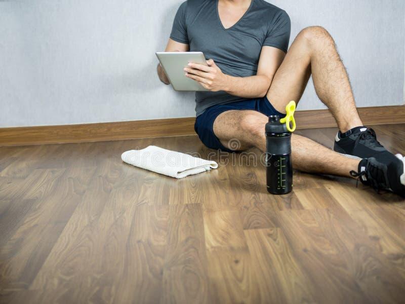 Man genom att använda minnestavlan för övning, sitt med sportvattenflaskan och handduken fotografering för bildbyråer