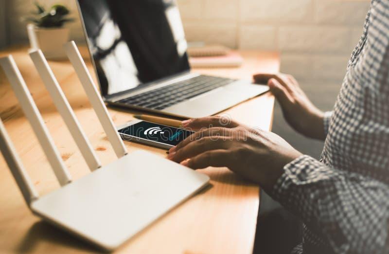 man genom att använda mobilen med förbinder wifi på skärmen Man` s räcker genom att använda apparaten det hemmastadda kontoret arkivbilder