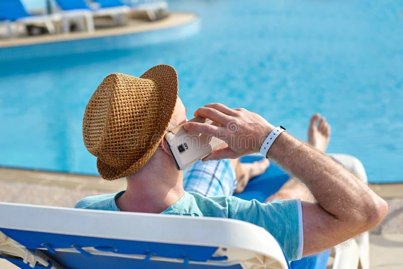 Man genom att använda mobiltelefonen på semester vid pölen i hotell, begrepp av en freelancer som arbetar för honom på semester o fotografering för bildbyråer