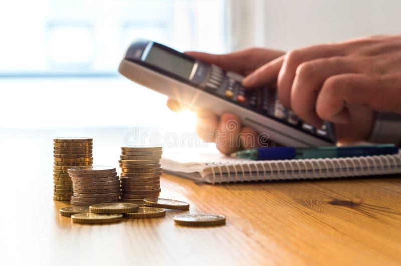Man genom att använda räknemaskinen för att räkna pengarbesparingar och bosatta kostnader arkivfoton