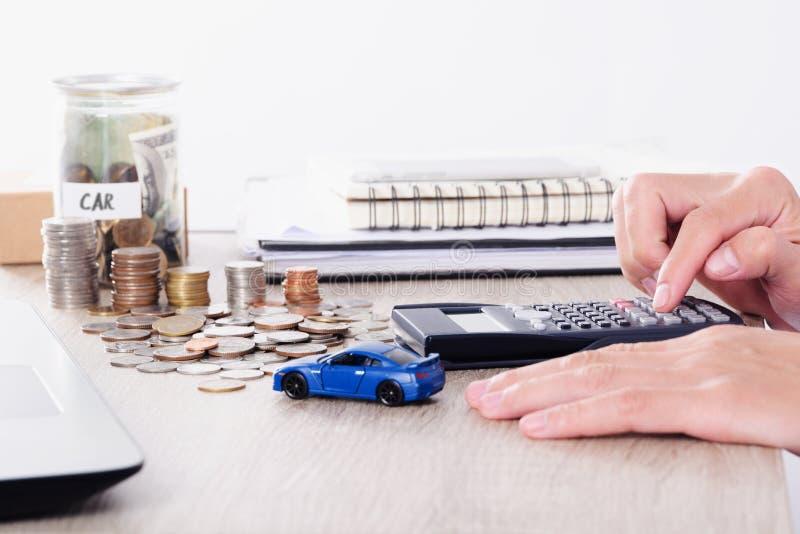 Man genom att använda räknemaskinen med billeksaken och mynta bunten för försäkringlån eller sparande för köpande bilbegrepp royaltyfri bild