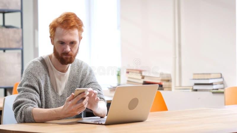 Man genom att använda Smartphone som direktanslutet bläddrar på arbete royaltyfri fotografi