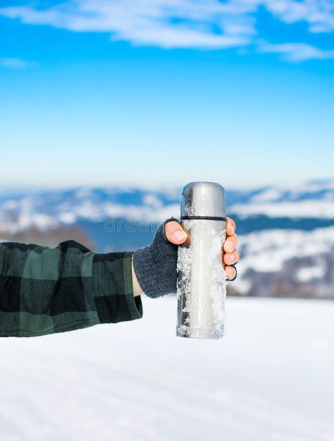 Man genom att använda termosflaskan på en vinterdag royaltyfria bilder