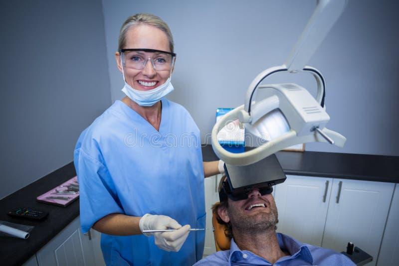 Man genom att använda virtuell verklighethörlurar med mikrofon under ett tand- besök arkivbild