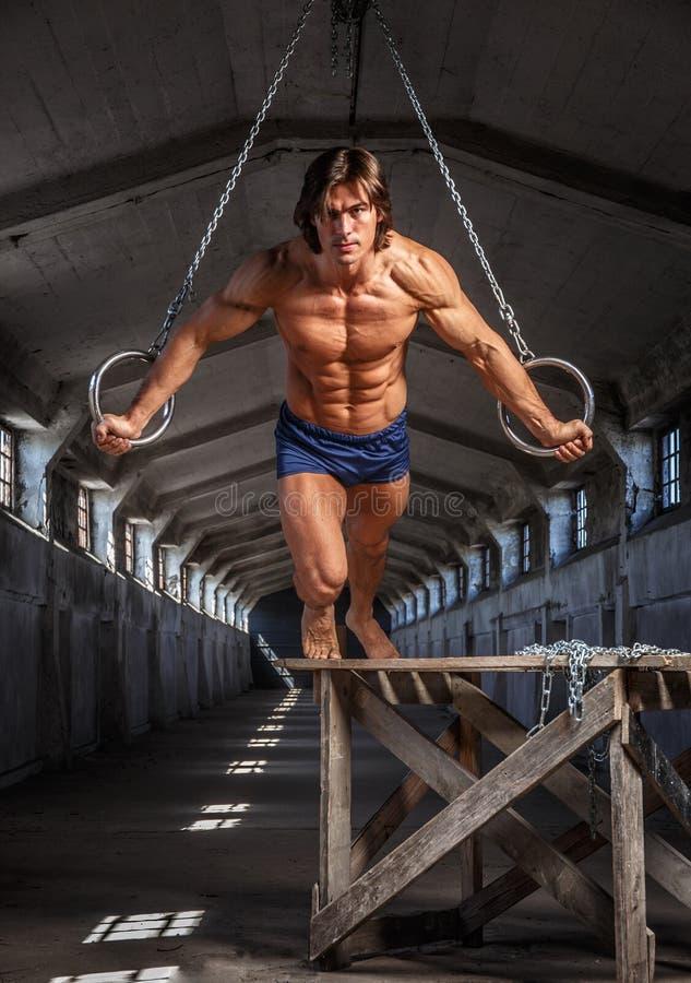 Man genomkörare i luften med gimnastic cirklar royaltyfri foto