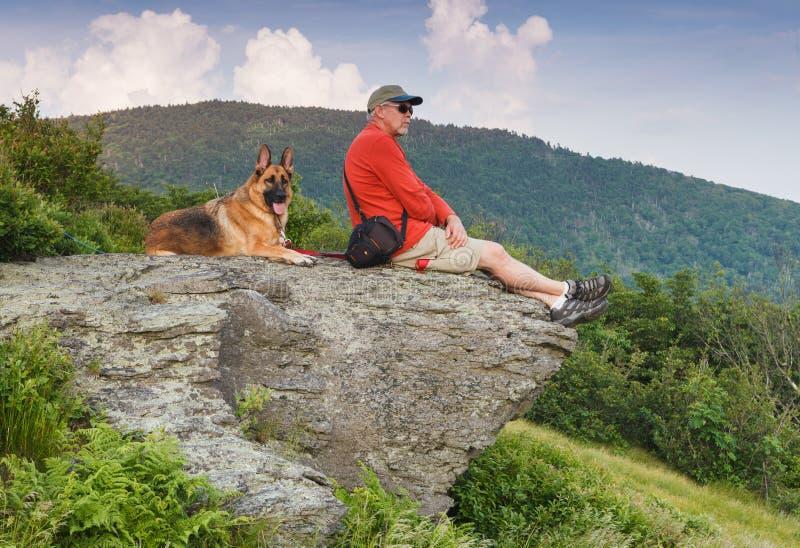 Man with German Shepherd Dog on Rock royalty free stock image