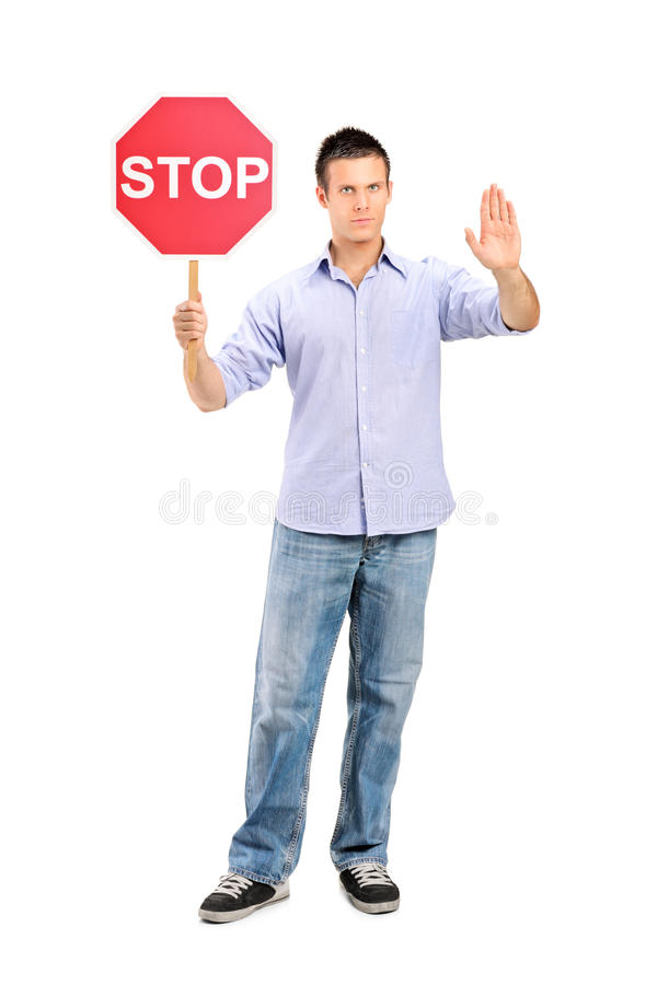Man gesturing and holding a traffic sign stop. Full length portrait of a man gesturing and holding a traffic sign stop on white background royalty free stock images