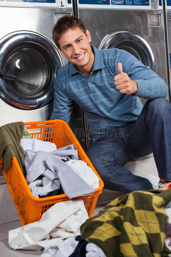 Download Man Gesturing Thumbs Up At Laundry Stock Photo - Image of appliance, laundromat: 37105050