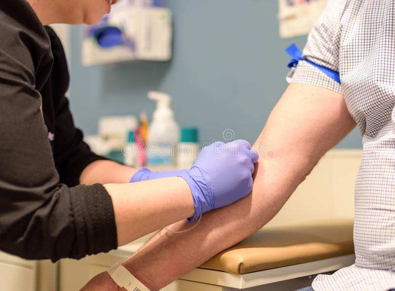 Man gets blood drawn at routine health screening. Closeup of a nurse drawing blood from a man`s arm at routine health screening royalty free stock photography