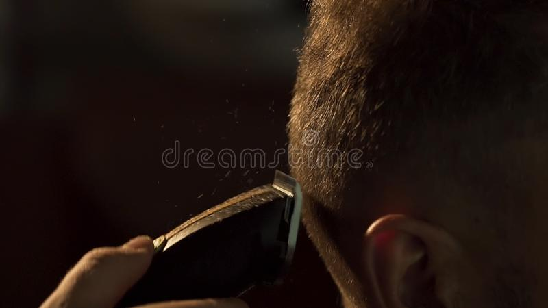 Man gets a cool haircut in barbershop. Frame. Hands of professional hair stylist cutting client shot hair. Close up of royalty free stock photo