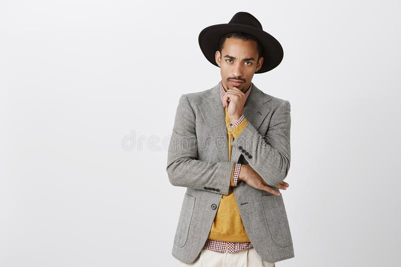 Man gets serious when it comes to job. Portrait of good-looking focused young dark-skinned male in stylish hat and royalty free stock photography