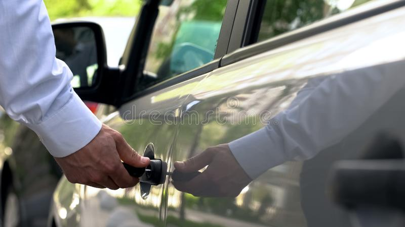 Man getting into auto, hurrying home after working day, parking in street. Stock photo stock images